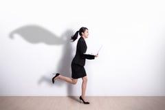 超级英雄女商人奔跑 免版税图库摄影