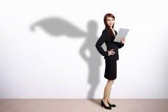 超级英雄有片剂的女商人 免版税库存照片