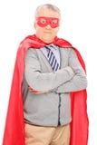 超级英雄服装摆在的老人 免版税图库摄影