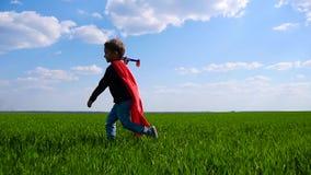 超级英雄服装的一个愉快的孩子横跨绿草跑,拿着玩具飞机,仿效飞行 股票视频