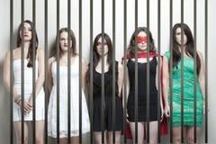 超级英雄服装的妇女有站立behinds监狱酒吧的女性朋友的 免版税库存照片