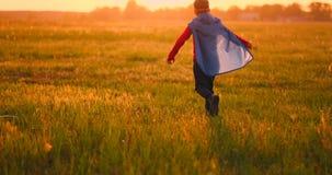 超级英雄服装的幻想跑横跨领域的男孩和面具在日落作梦和 影视素材