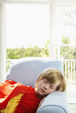 超级英雄服装的逗人喜爱的男孩睡觉在扶手椅子的 库存图片