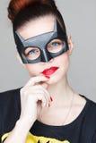 超级英雄面具的一个美丽的年轻美丽的女孩在灰色背景的演播室 图库摄影