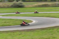 超级kart赛跑的队 用车运送的竟赛者 库存照片