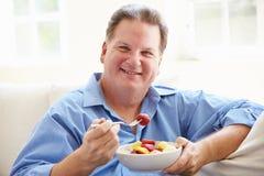 超重人坐吃碗新鲜水果的沙发 免版税库存图片