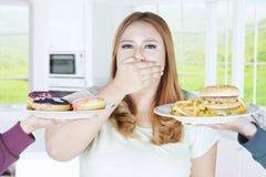 超重卡路里食物的妇女闭合的嘴 库存图片