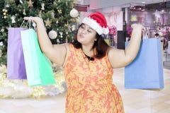 超重在购物中心的妇女举的圣诞节礼物 免版税图库摄影