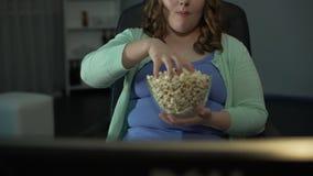 超重女性采取的极少数玉米花和在家吃在电视前面 股票视频