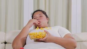 超重妇女吃玉米花并且看起来困 股票录像
