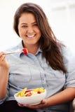 超重妇女坐吃碗新鲜水果的沙发 库存图片