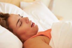 超重妇女睡着在打鼾的床上 库存照片