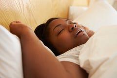 超重妇女睡着在打鼾的床上 免版税库存照片