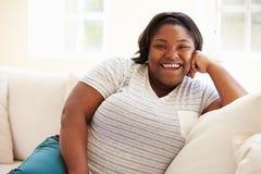 超重妇女画象坐沙发 免版税库存照片