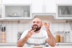 超重年轻人用不健康的食物在桌上 免版税库存图片