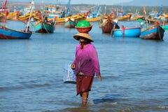 越南妇女沿海的沿海小条有物品的走在她的头 美奈,越南钓鱼海港  库存照片