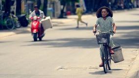 越南妇女骑马自行车在会安市 库存照片