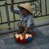 越南妇女,卖灯笼蜡烛,为满月灯会,在古镇 库存图片