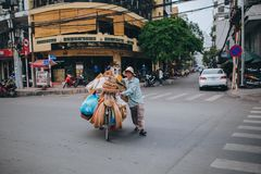 越南有袋子和篮子的人运载的自行车在路在胡志明,越南 免版税库存图片