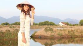 越南服装和帽子的白肤金发的女孩在池塘附近摆在 股票视频