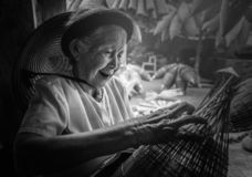 越南渔夫做着捕鱼设备的编织品在 免版税库存图片