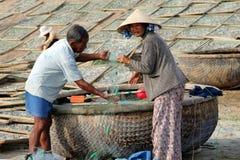 越南渔夫在圆的柳条小船Thung柴附近检查捕鱼网 免版税库存照片