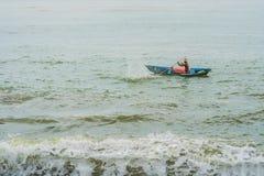 越南渔夫在汹涌的海的一条小船游泳 库存图片