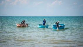 越南渔夫拉扯他们的渔小圆舟到钓鱼的海在渔夫村庄,美奈,越南 免版税库存图片