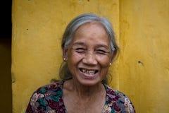 从越南的老妇人微笑在街道上的 库存照片