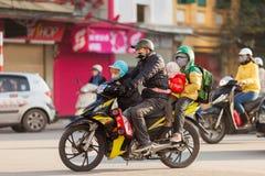 越南,父亲乘坐有三个孩子的摩托车 图库摄影