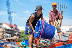 越南, PHU QUOC - 2014年11月3日:越南渔夫在Duong东港口golding站立在小船的塑料篮子 库存照片