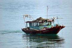 越南-下龙湾-去的钓鱼在一个绿色渔船 免版税库存图片