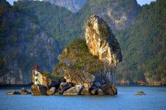 越南-下龙湾-在前景的晚上轻的小特别石灰石石灰岩地区常见的地形与更大的海岛在背景中 库存照片