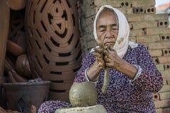 越南2017年12月:从黏土混合物在她的工厂,越南的地方越南妇女造型罐 库存照片