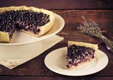 越桔,蓝莓馅饼用在白色板材,木背景的淡紫色 图库摄影