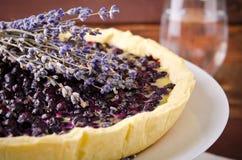 越桔,蓝莓馅饼用在白色板材,木背景的淡紫色 免版税图库摄影