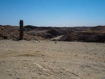 越野旅途通过纳米比亚沙漠独特的地理巨大岩石山风景背景与石地面路的 库存照片