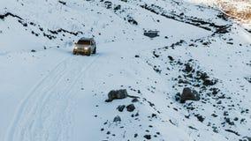 越野汽车下降一座积雪覆盖的山的倾斜 图库摄影