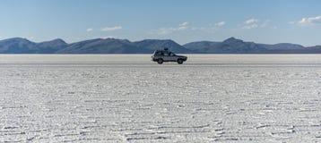 越野汽车在撒拉族de Uyuni是最大的盐平在世界联合国科教文组织世界遗产名录站点- Altiplano,玻利维亚 库存图片