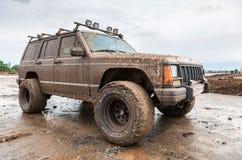 越野车在驾驶在极端肮脏的ru的雨中以后 免版税库存图片