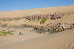 越野野营在纳米比亚和安哥拉的参天的古老纳米比亚沙漠沙丘的前面Kunene河 免版税库存图片