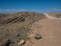 越野驾车在旅行在美好的阳光天通过在沙漠岩石山风景中的多灰尘的未铺砌的路线 图库摄影