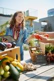 趋向一个有机菜摊位在农夫的市场上和卖从屋顶的友好的妇女新鲜蔬菜 库存图片