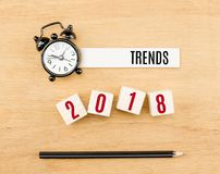 趋向在木立方体的2018年有在木桌上的铅笔和时钟顶视图,新年企业概念 免版税库存图片