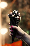 趋向木炭与五彩纸屑和食物粉末,桃红色和蓝色蓬松甜点的冰淇凌锥体在妇女` s胳膊 被弄脏的Bokeh 库存图片