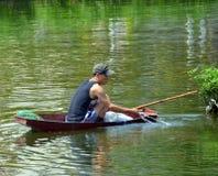 趋向他的在一条小船的渔夫网在西湖在河内 免版税库存照片