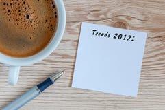 趋向2017年被写在笔记薄在桌工作场所在杯子早晨咖啡附近 新年企业和时尚trendings 库存照片