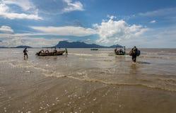趟过在海滩的水中的人们有小船从Bako国家公园返回在婆罗洲 免版税图库摄影