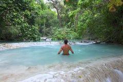 趟过在热带天堂水池的人 库存照片