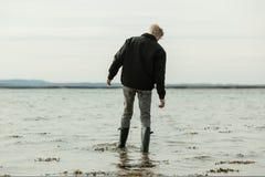 趟过在水中的男孩移动在大浪期间 库存图片